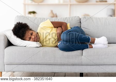 Stomachache. Black Teen Girl Suffering From Abdominal Pain Touching Aching Stomach Lying On Sofa At