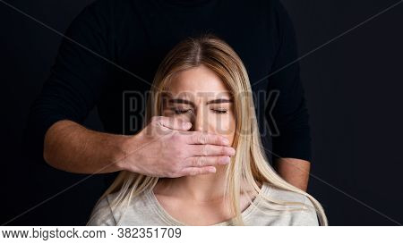 Psychological And Physical Pressure Man On Woman. Male Hand Closes Mouth Of Sad Woman With Closed Ey