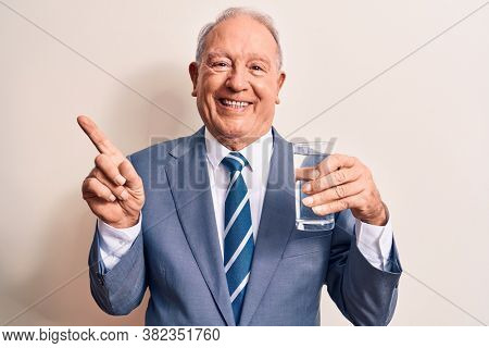 Senior handsome grey-haired businessman wearing suit drinking glass of water to refreshment smiling happy pointing with hand and finger to the side