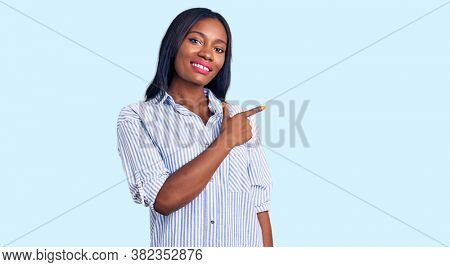 Young african american woman wearing casual clothes cheerful with a smile of face pointing with hand and finger up to the side with happy and natural expression on face