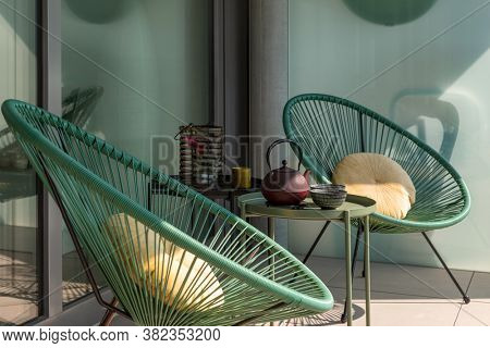 Elegant corner of a terrace of a modern house with two armchairs and a Chinese tea with two cups. Sunny summer day