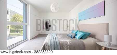 Elegant bedroom with white walls, double bed and lots of pillows. Nobody inside