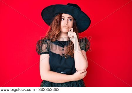 Young beautiful woman wearing witch halloween costume thinking concentrated about doubt with finger on chin and looking up wondering