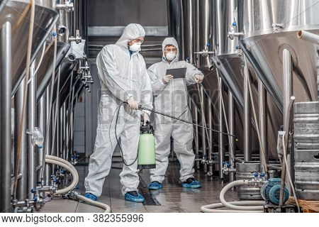 Work On Brewery Factory. Two Men In Protective Suits And Masks Handle With Equipment At Plant And Di