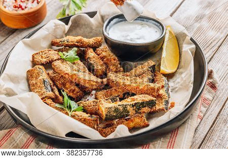Crispy Zucchini Sticks With Yogurt Dip On Rustic Wooden Background. Healthy Snack. Selective Focus