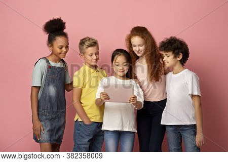 Multinational Young Students Using Tablet Computer To Study Together On Pink Background