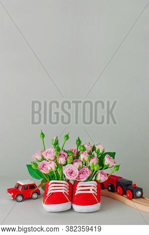 Baby Shoes Filled With Rose Flowers And Toys
