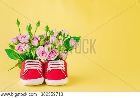 Baby Shoes With Rose Flowers On Yellow Background With Copy Space