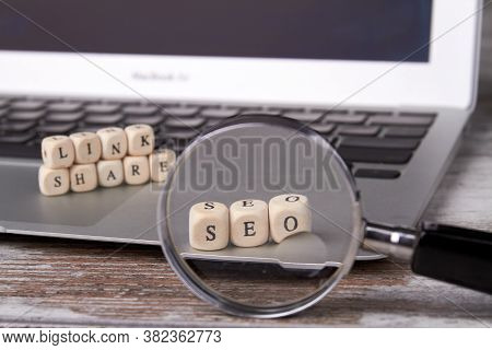 Looking Through A Magnifying Glass On Seo Blocks. Wooden Cubes With Letters On The Laptop. Link Shar