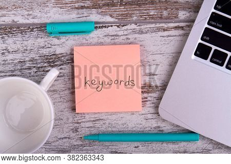 Keywords For Web Optimization. Pen, White Cup And Laptop On Wooden Table.