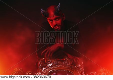 A portrait of a red horned devil standing leaning on a vintage armchair.  Horror movie, nightmare. Halloween. Horror movie, nightmare. Halloween.