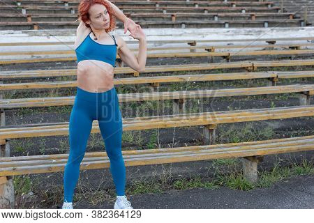 Portrait Of A Red-haired Female Athlete, Thirty-six Years Old, In A Turquoise Sports Uniform, Doing