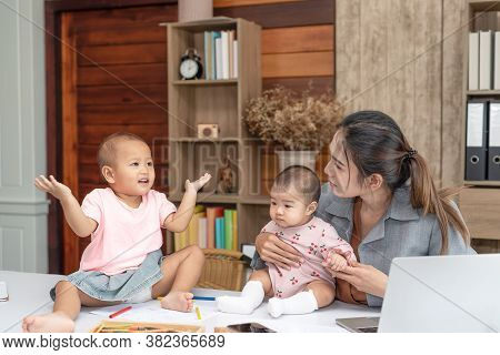 Busy Woman Trying To Work While Babysitting Two Daughter.  Young Beautiful Asian Mother Holding Litt