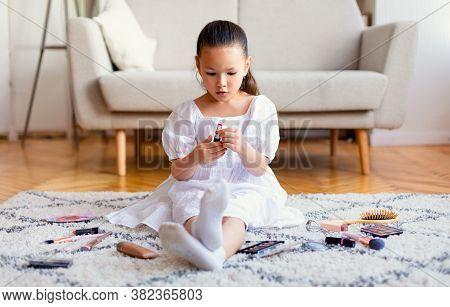 Cute Korean Kid Girl Making Makeup Playing With Moms Lipstick Sitting On Floor At Home. Girlhood Fun