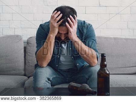 Despair And Alcoholism. Sad Man Alcoholic Holds His Head With Hands, Empty Bottles On Table In Inter