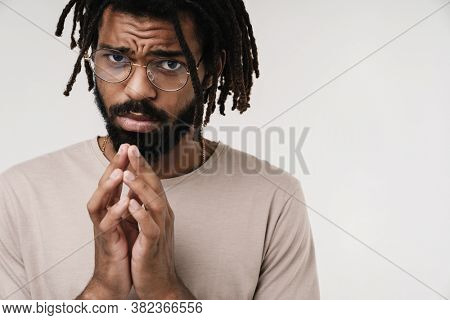 Image of guilty hopeful african guy isolated over grey wall background in eyeglasses