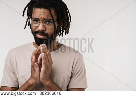 Image of confused guilty african guy isolated over grey wall background in eyeglasses