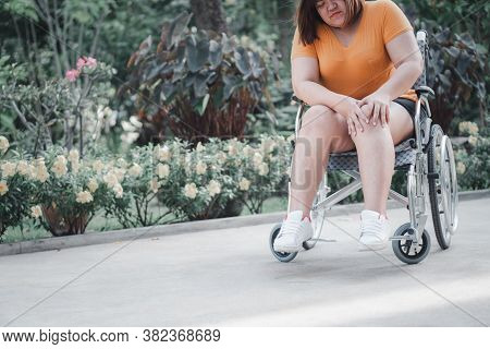 Overweight And Obesity Woman Sitting On Wheelchair And Holding Her Knee In Pain, Cause Of Inflammati