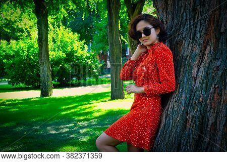 Happy Girl In Red Dress Leaning Park Tree In Summer