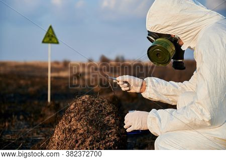Ecologist In Gas Mask Studying Burnt Grass And Soil On Scorched Territory With Biohazard Sign. Envir
