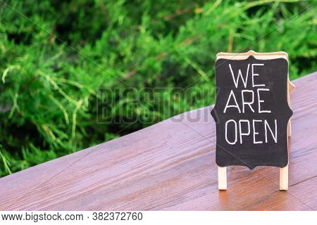 Handwritten Text We Are Open On Blackboard Closeup On Cafe Wooden Table Outdoors. Open Sign In Open-