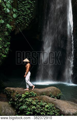 A Man Of Athletic Build At The Waterfall. A Man Travels The World. Man At The Waterfall. Travel To B