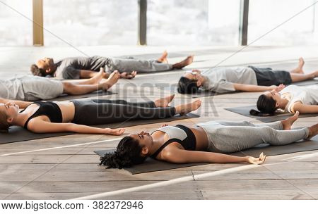 Group Of Sporty People Relaxing During Yoga Lesson, Lying On Floor In Corpse Pose, Doing Shavasana,