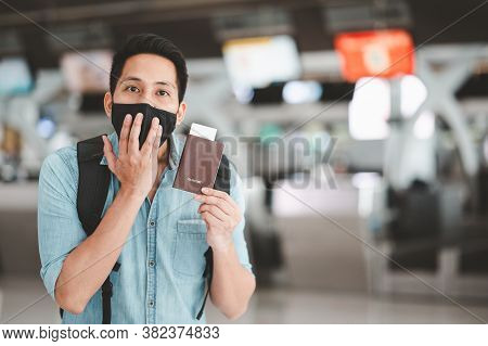 Tried Asian Man Wearing Face Mask Resting Or Sleeping On The Floor Of Airport Terminal Waiting For T