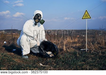 Portrait Of Ecologist In Protective Suit And Gas Mask. Research Scientist Picking Up Garbage In Gras