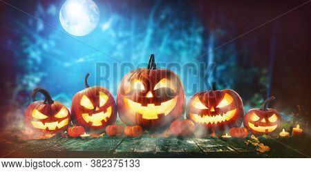 Halloween pumpkin head jack-o-lantern in front of a spooky forest