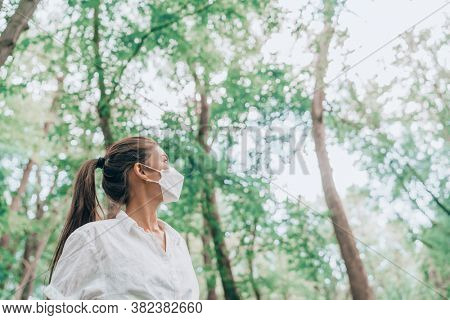 Woman hiking in forest nature wearing face mask while walking outdoors, looking up at trees in hope. Clean air, sustainability, eco-friendly masks for coronavirus protection concept.