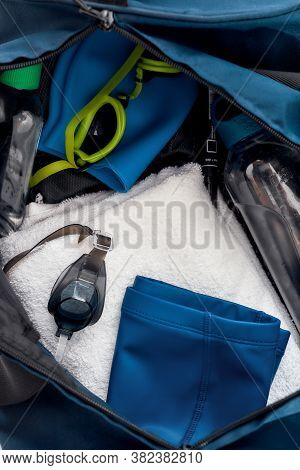 Swimming Pool Set. Close Up Shot Of Sports Bag With Swim Goggles, Hat Or Cap, Towel And Bottle Of Wa