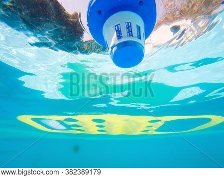 Underwater View Of Chlorine Dispenser And Air Mattress In A Pool Seen From Below