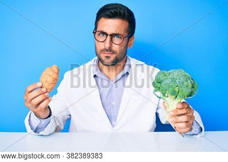 Young hispanic man as nutritionist doctor holding croissant and broccoli skeptic and nervous, frowning upset because of problem. negative person.