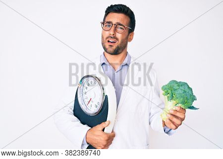 Young hispanic man as nutritionist doctor holding weighing machine and broccoli clueless and confused expression. doubt concept.