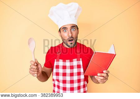 Young hispanic man wearing professional baker apron reading cooking recipe book in shock face, looking skeptical and sarcastic, surprised with open mouth