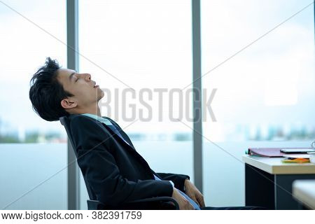Businessman Sitting At Workplace Near Feeling Tired Exhaustion And Tiredness After Long Hard Working