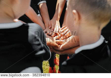 Group Of Sports Team Forming A Huddle With Their Hands. Kids Sports Team Stacking Hands Together Bef