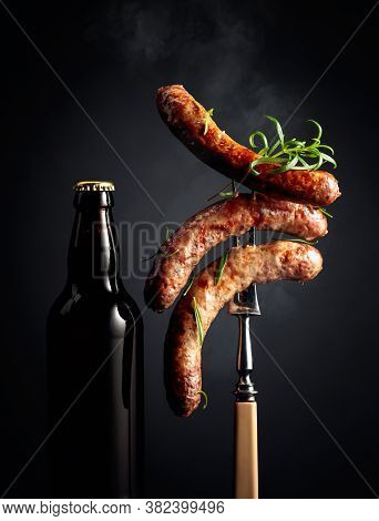Beer And Grilled Sausages With Rosemary. Sausages On A Fork Sprinkled With Rosemary.