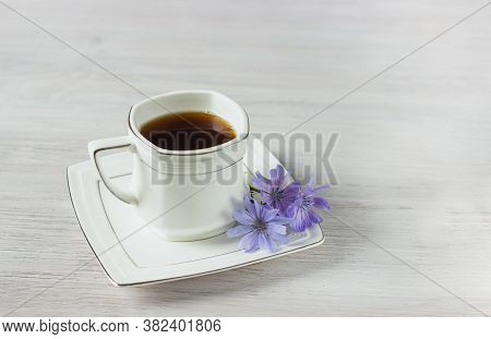 White Cup Of Instant Chicory Drink Or Coffee With Chicory Flowers On A White Table. Hot Drink. Healt