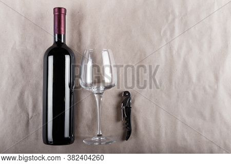 Wine Set - A Closed Bottle Of Red Wine With A Corkscrew And A Glass On A Gray Background
