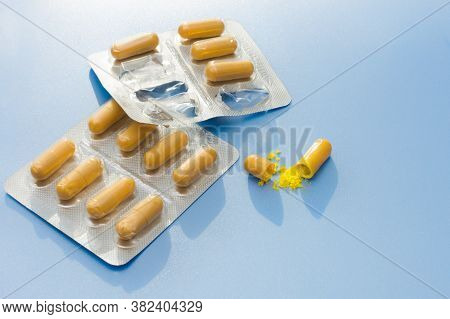 Close-up On A Blue Background Yellow Capsules In A Blister, Started Packaging And One Open Capsule.