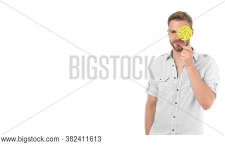 Check Your Vision. Man Holds Big Lollipop In Front Of Eye. Guy Concentrated Face Passing Vision Test