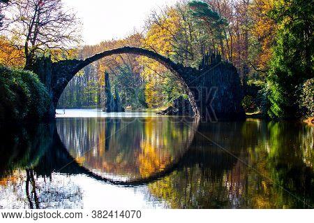 Spectacular Autumn Season In Azalea And Rhododendron Park Kromlau. Rakotz Bridge, Rakotzbrucke Devil