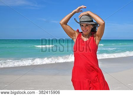 Beautiful Mature Woman Wearing A Red Summer Dress On The Beach Holding Her Hat On In The Wind