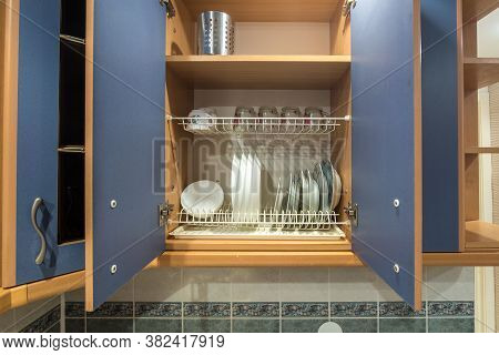 Set Of Plates, Cups, Knives, Forks And Wine Glasses On The Shelf In The Kitchen Cabinet