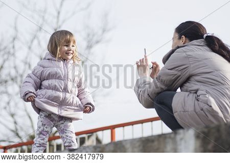 The Mother Is Photographing Her Cute Posing Daughter In Jacket Outdoors.