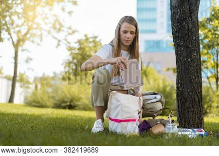 Young Student Woman With Books Spends Free Leisure Time While Sitting On The Grass Outside In Park.