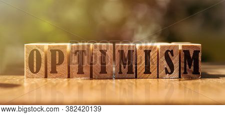 Optimism Word Written In Wooden Cubes In Sunlight. Positive Concept