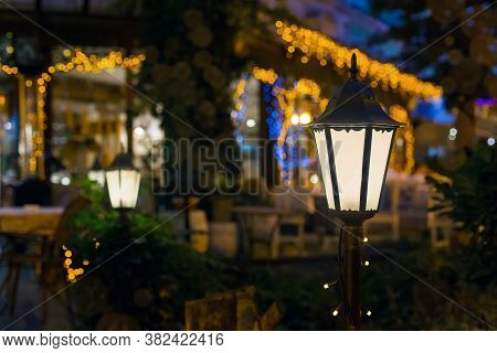Iron Retro Lantern Of Cafe Lighting Glowe With Warm Light In The Night Garden Of The Backyard In The